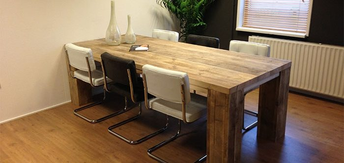 Een steigerhouten tafel met zes aangeschoven stoelen en een plantenbak achter de steigerhouten tafel.